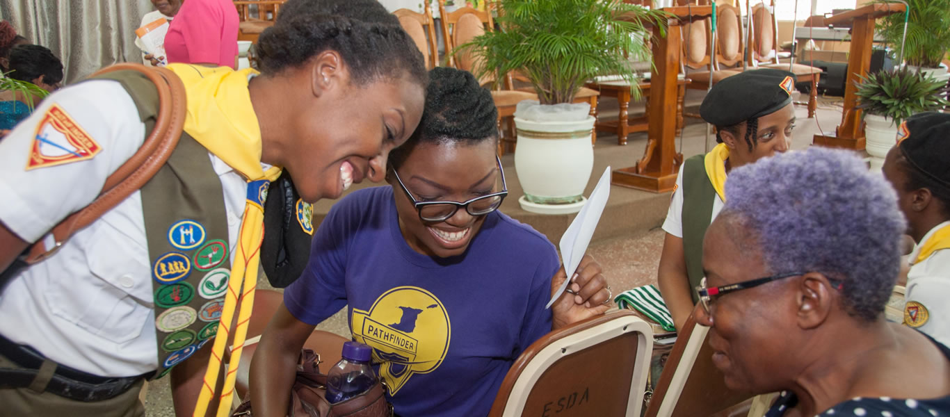 <strong>Love in Action</strong>         <br/>Pathfinders sharing a gift with an elderly member during a visit to Enterprise, Trinidad.